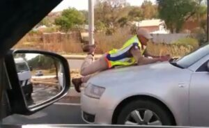 Watch: Woman arrested for driving with traffic cop hanging on her bonnet