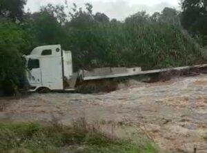 Watch: Truck swept off flooded bridge